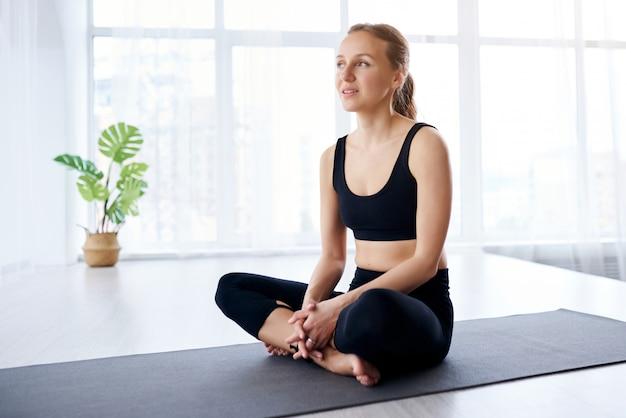 Молодая красивая женщина, занимаясь йогой в современной светлой комнате с большими окнами. учитель йоги объясняет, как делать асаны.