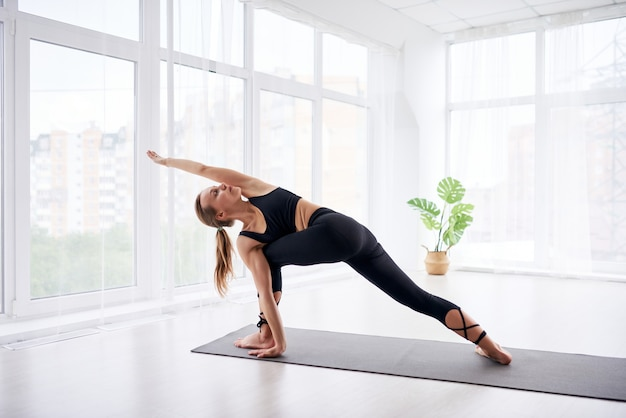 Young beautiful woman doing yoga in a modern bright room with large windows. yoga at home concept.