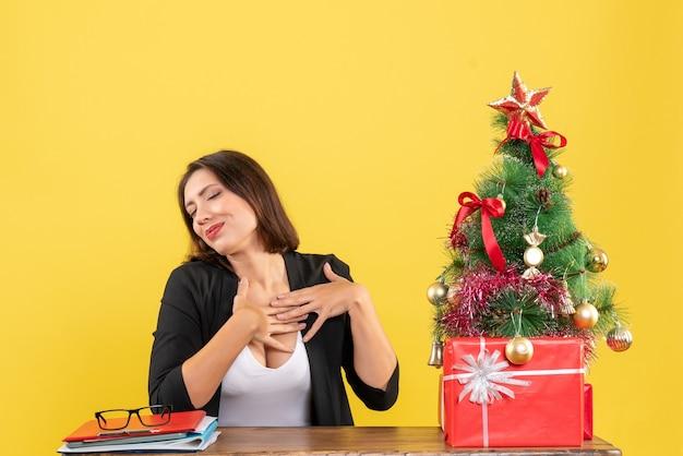 Giovane bella donna che sogna qualcosa con attenzione seduto a un tavolo vicino all'albero di natale decorato in ufficio su giallo