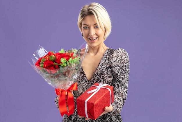 Giovane bella donna in abito tenendo presente e bouquet di rose rosse guardando la telecamera felice e allegro sorridente ampiamente il giorno di san valentino concetto in piedi sopra il muro viola