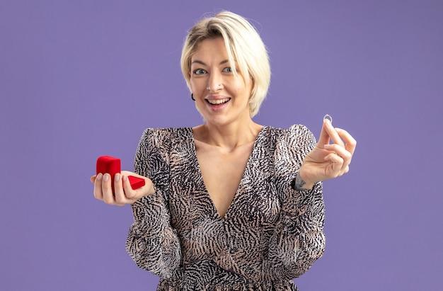 Giovane bella donna in abito che tiene scatola rossa con anello di fidanzamento guardando la fotocamera felice ed eccitato sorridendo allegramente il giorno di san valentino concetto in piedi su sfondo viola