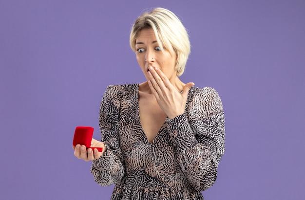 Giovane bella donna in vestito che tiene scatola rossa con anello di fidanzamento guardandolo stupito e sorpreso il concetto di san valentino in piedi sul muro viola