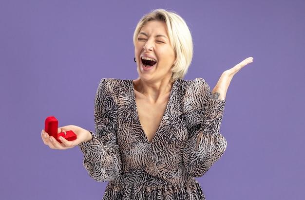 Giovane bella donna in vestito che tiene scatola rossa con anello di fidanzamento urlando felice ed eccitato il giorno di san valentino concetto in piedi sul muro viola
