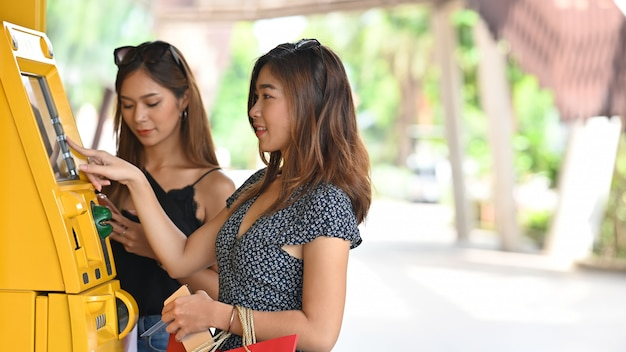 Young beautiful woman in dress holding a shopping bags and entering an password at the yellow auto teller machine next to her friend that looking good in black singlet at the shopping center.