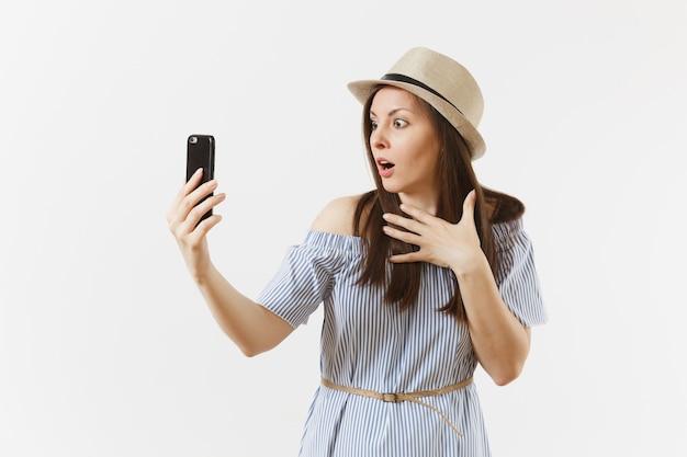 파란 드레스를 입은 젊고 아름다운 여성, 흰색 배경에 격리된 휴대전화 또는 화상 통화로 셀카를 찍는 모자를 쓰고 있습니다. 사람, 진실한 감정, 라이프 스타일 개념. 광고 영역입니다. 공간을 복사합니다.