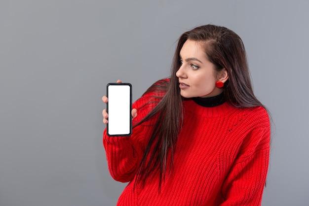 赤いセーターを着た若い美しい女性は、灰色で隔離の彼女のスマートフォンを示しています