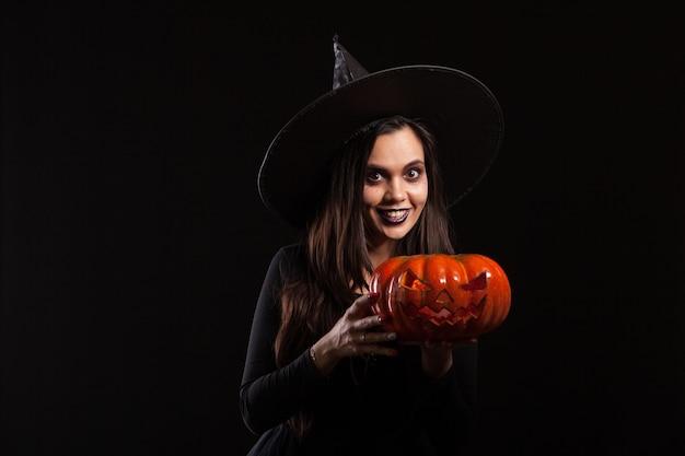 Молодая красивая женщина, одетая как ведьма на хэллоуин. молодые с тыквой в руках. ведьма улыбается.