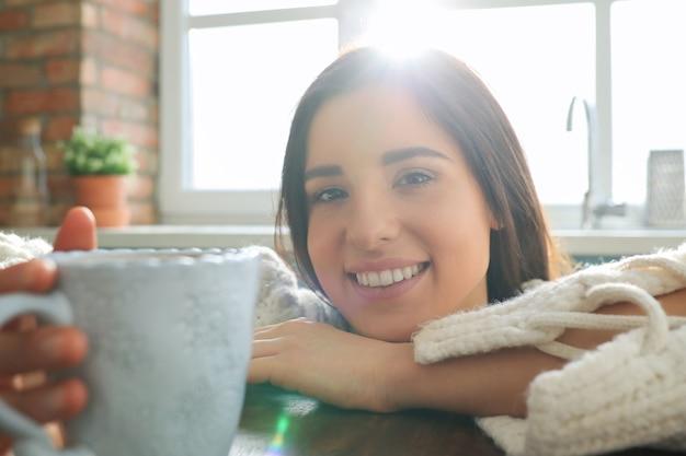 台所で温かい飲み物を飲む若い美しい女性