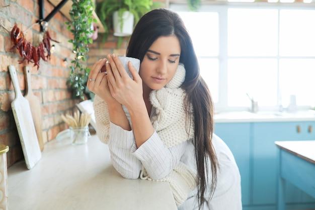 Молодая красивая женщина пьет горячий напиток на кухне