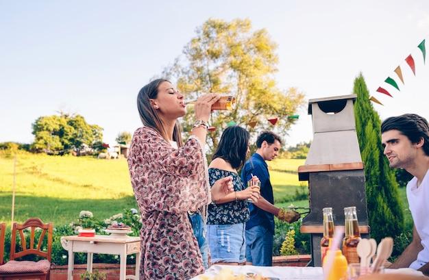 야외 여름 바비큐에서 친구들과 맥주 한 병을 마시는 젊은 미녀