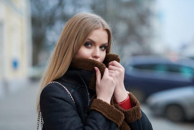 커피를 마시고 도시를 걷는 젊은 아름 다운 여자