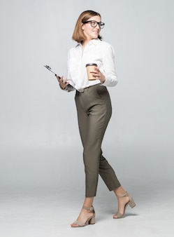 Young beautiful woman drinking coffee holding clipboard posing isolated over white wall wall