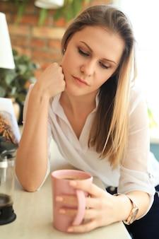 Молодая красивая женщина пьет кофе или чай