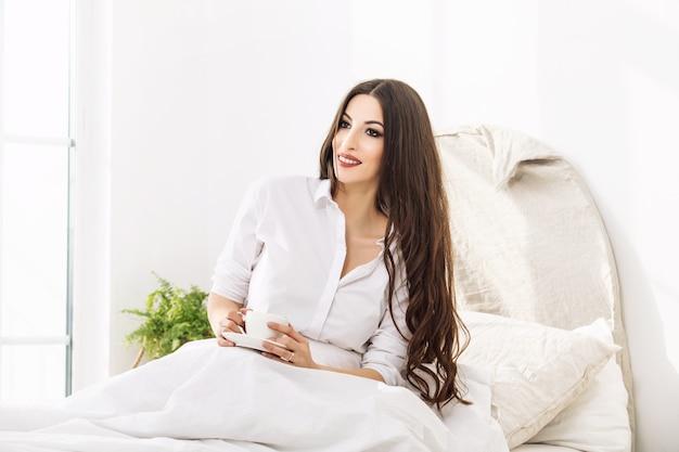 白いシャツを着て寝室の自宅でホットドリンクのマグカップから飲む若い美しい女性