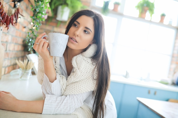 Young beautiful woman drinking a hot drink in the kitchen