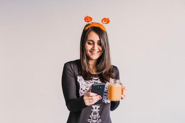 Молодая красивая женщина, пить апельсиновый сок и принимая selfie с мобильного телефона. одет в черно-белый костюм скелета. концепция хэллоуин в помещении