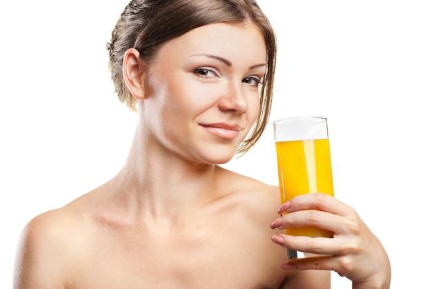 白い背景で隔離のオレンジジュースを飲む若い美しい女性
