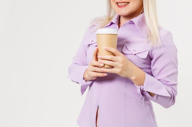 격리 된 흰색 배경 위에 커피 종이 잔을 마시는 젊은 아름 다운 여자 프리미엄 사진