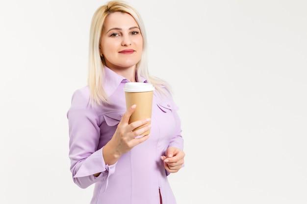 격리 된 흰색 배경 위에 커피 종이 잔을 마시는 젊은 아름 다운 여자