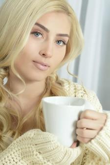 Молодая красивая женщина пьет чай дома