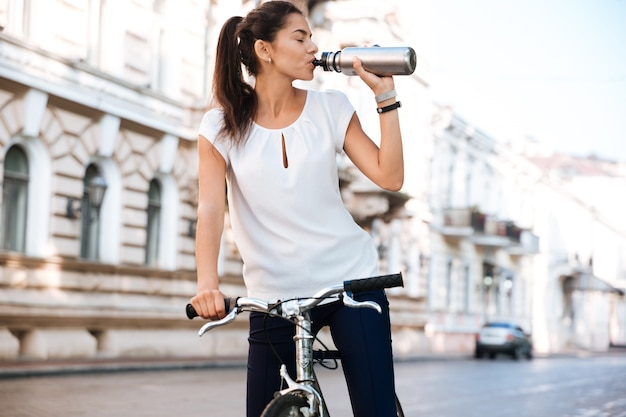 Young beautiful woman drinking water from the bottle while riding bicycle