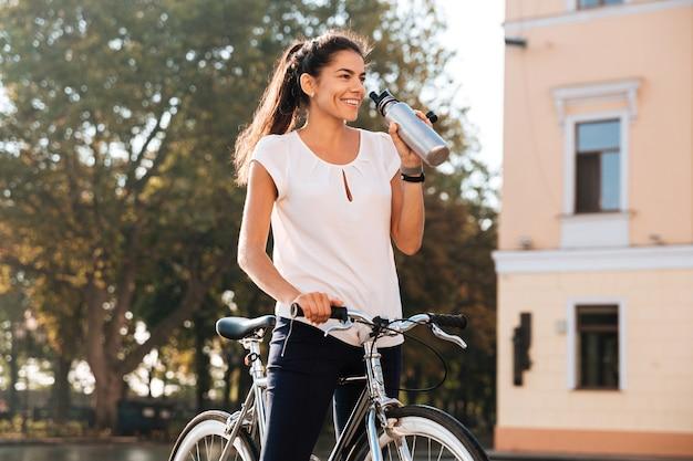 Молодая красивая женщина пьет воду из бутылки и сидит на велосипеде