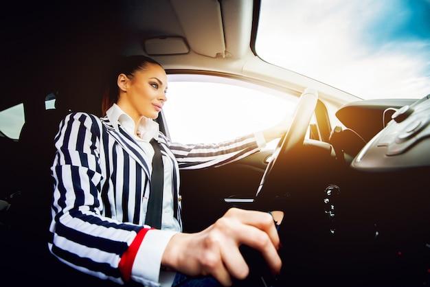 Young beautiful woman driving a car shifting gear.