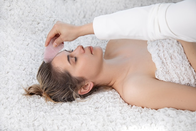 Young and beautiful woman during chinese traditional massage - gua sha with stone. beauty treatment in spa salon. anti-aging skin care