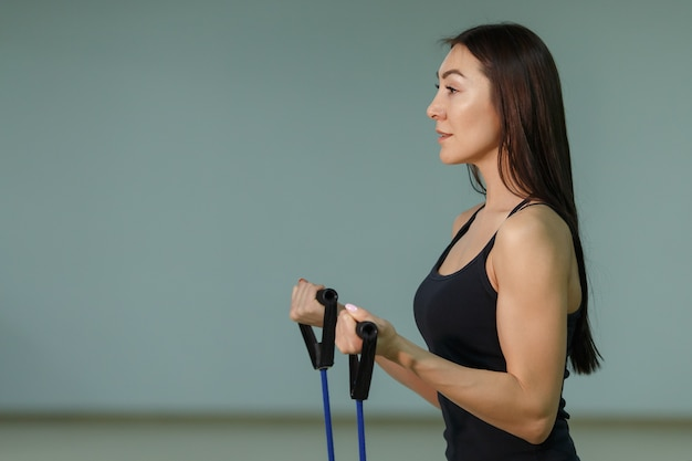 Young beautiful woman during fitness with expander.