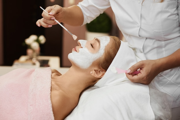 Young beautiful woman during spa, while hands of female cosmetologist applying peel mask to her face with a wide brush. model girl with scrub on her face.