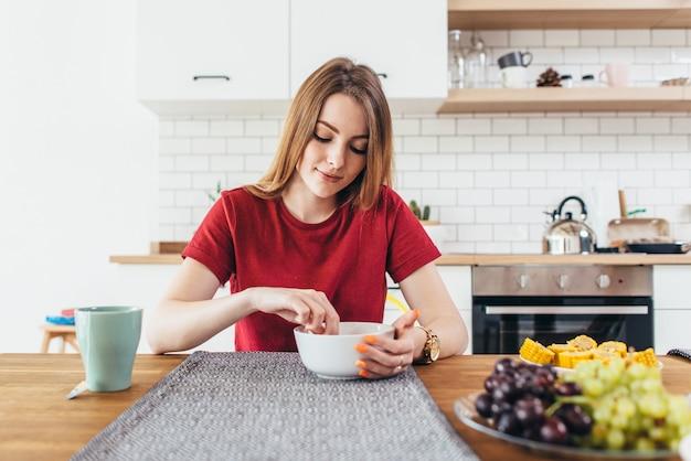 台所で果物や野菜の健康食品を食べる若い美しい女性。