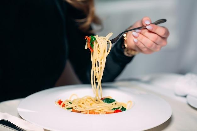 Молодая красивая женщина ест макароны в ресторане.