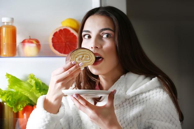 밤에 냉장고에서 건강에 해로운 음식을 먹는 젊은 미녀