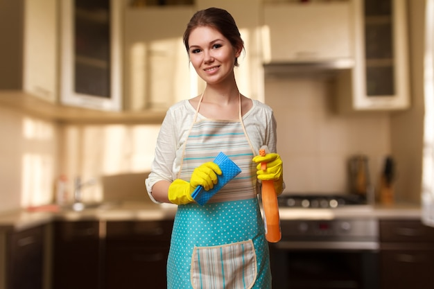 Young beautiful woman engaged in cleaning the kitchen