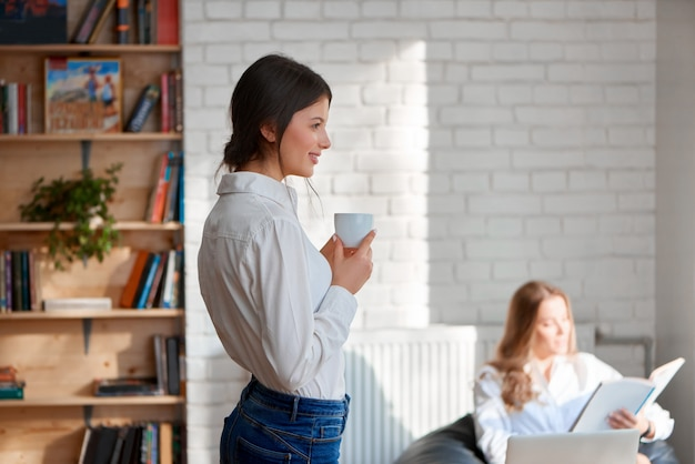 Young beautiful woman enjoying a cup of coffee smiling looking away her colleague working on a laptop copyspace office cafe coffee shop workplace teamwork studying learn.