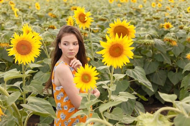 푸른 하늘에 해바라기를 들고 여름, 젊음, 자유를 즐기는 젊은 아름 다운 여자. 이미지 톤.