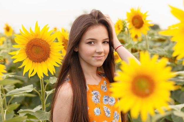 Young beautiful woman enjoying summer, youth and freedom, holding sunflowers against blue sky. image toned.