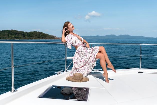 Young beautiful woman enjoys a summer yacht cruise