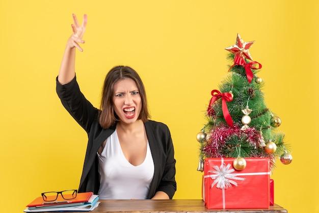 노란색에 사무실에서 장식 된 크리스마스 트리 근처 테이블에 감정적으로 앉아 뭔가를 설명하는 젊은 아름 다운 여자