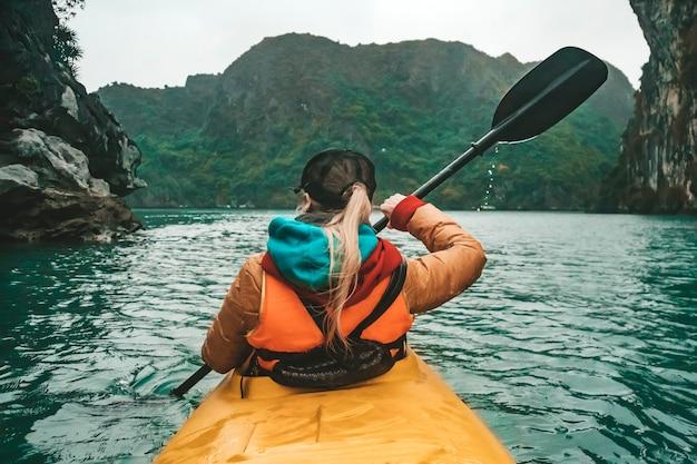Молодая красивая женщина плывет на байдарке между скалами, торчащими из моря. девушка гребет на веслах на фоне красивого морского пейзажа. водные активные виды спорта.