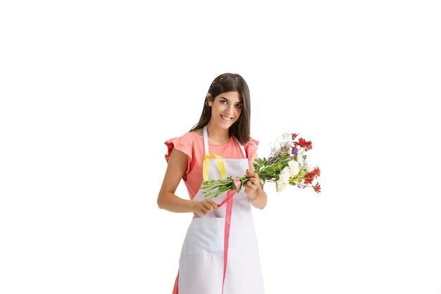 若い美しい女性、白いスタジオで隔離のカラフルな新鮮な花束を持つ花屋