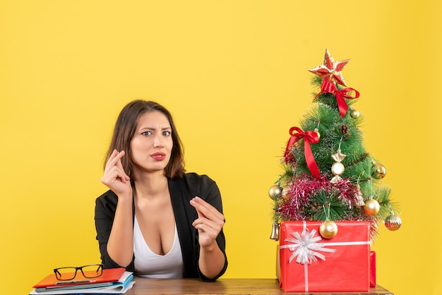 노란색 사무실에서 장식 된 크리스마스 트리 근처 테이블에 신중하게 앉아 뭔가에 초점을 맞춘 젊은 아름 다운 여자