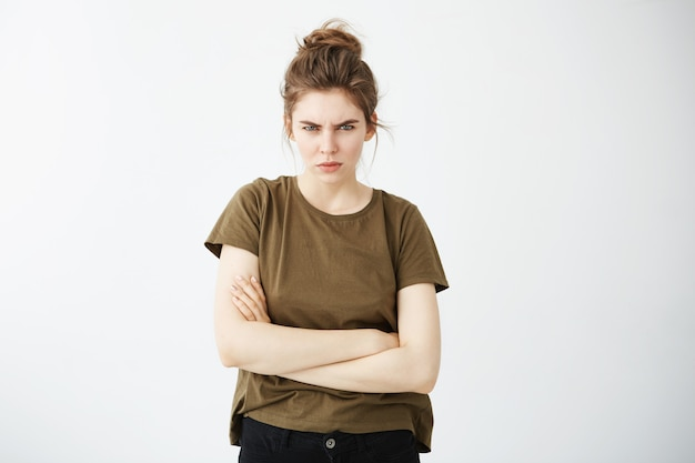 Young beautiful woman frowning with crossed arms