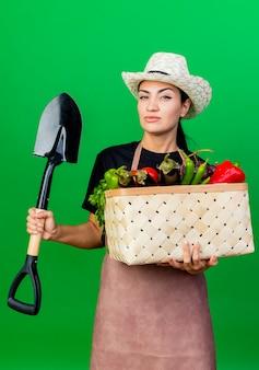 Giardiniere giovane bella donna in grembiule e cappello tenendo il cesto pieno di verdure e pala con la faccia seria