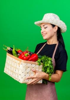 Giardiniere della giovane bella donna in grembiule e cappello che tiene il cestino pieno di verdure che sorride con la faccia felice