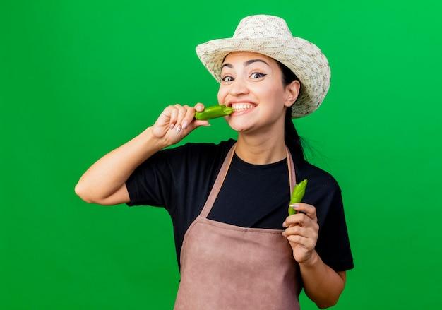 Giardiniere della giovane bella donna in grembiule e cappello che tengono peperoncino verde rotto andando a morderlo