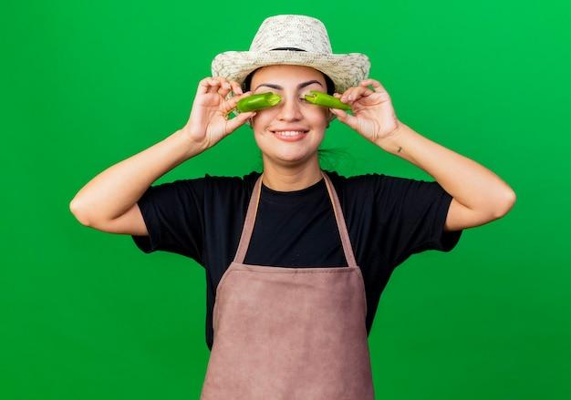 Giardiniere della giovane bella donna in grembiule e cappello che tengono peperoncino verde rotto sopra i suoi occhi che sorridono