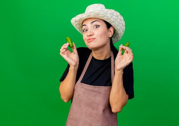Giardiniere della giovane bella donna in grembiule e cappello che tengono peperoncino verde rotto con l'espressione scettica