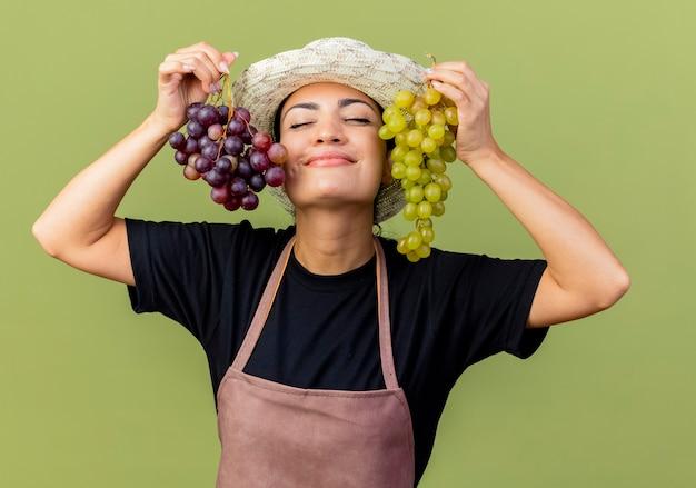 Giardiniere di giovane bella donna in grembiule e cappello che tiene i grappoli d'uva con gli occhi chiusi, provare emozioni positive in piedi sopra la parete verde chiaro