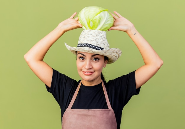 Giardiniere della giovane bella donna in grembiule e cappello che tiene il cavolo sulla sua testa sorridente guardando la parte anteriore in piedi sopra la parete verde chiaro